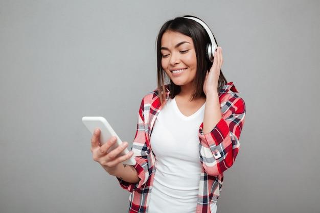 Junge glückliche frau, die musik mit kopfhörern hört.