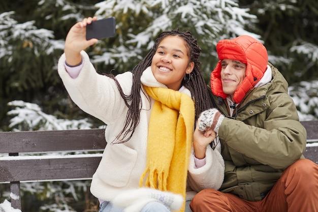 Junge glückliche frau, die selfie auf ihrem handy mit ihrem freund macht, während sie auf bank im winter sitzen