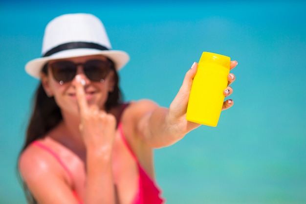 Junge glückliche frau, die sonnenschutzmittel auf ihrer nase auf weißem strand anwendet