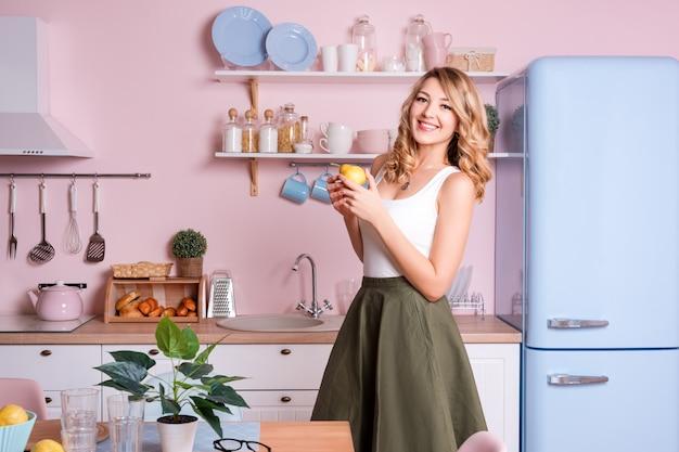 Junge glückliche frau, die zu hause früchte in der küche isst. blondes schönes mädchen, das ihr frühstückt, bevor es zum büro geht. rosa und blauer moderner küchenpastellinnenraum.