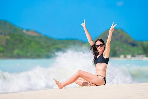 Junge glückliche frau im badeanzug am weißen strand. schönes modell im bikini, der sich hinsetzt.