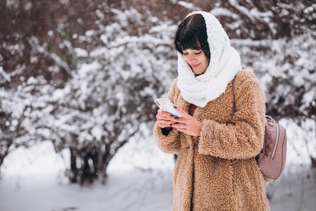 Junge glückliche frau in den warmen stoffen in einem winterpark