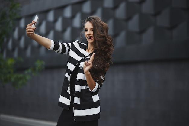 Junge glückliche frau in einem schwarzweiss-kleid, das ein selfie mit einem handy macht