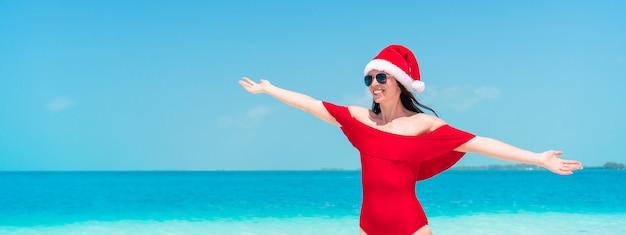Junge glückliche frau in sankt-hut im badeanzug auf weißem strand an weihnachtsfeiertagen