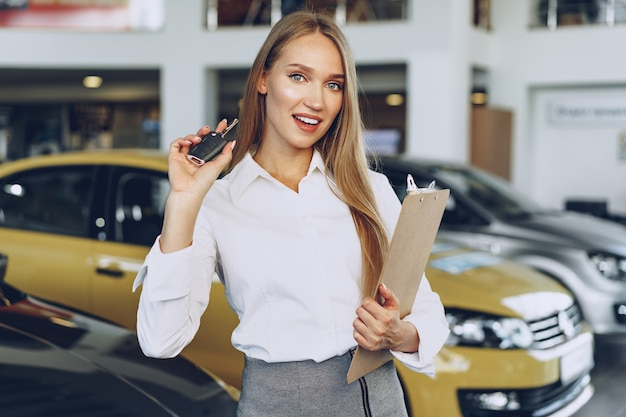 Junge glückliche frau käufer nahe dem auto mit schlüsseln in der hand