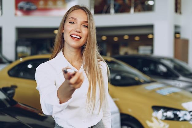 Junge glückliche frau käufer / verkäufer in der nähe des autos mit schlüsseln in der hand