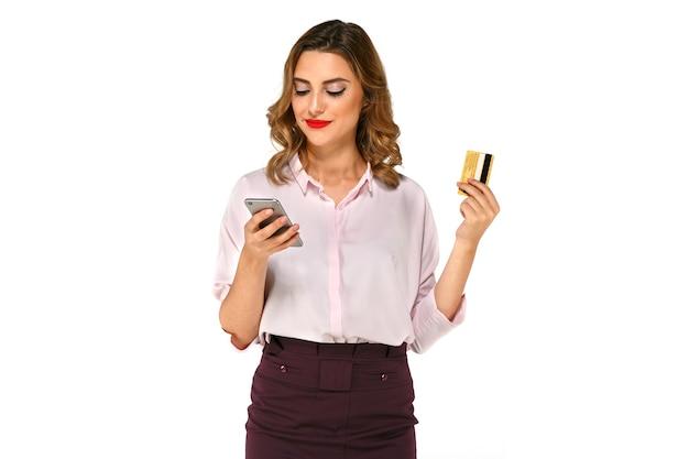 Junge glückliche frau macht käufe in app auf smartphone und zahlt mit kreditkarte