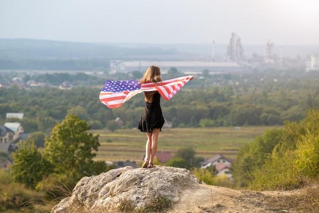 Junge glückliche frau mit dem langen haar, das das winken auf der amerikanischen windnationalflagge in ihren händen aufsteht, die auf hohem felsigem hügel stehen, der warmen sommertag genießt.