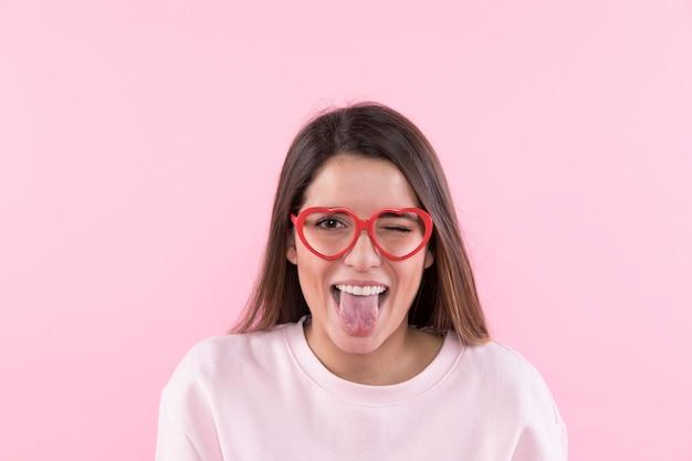 Junge glückliche frau mit den brillen, die zunge zeigen