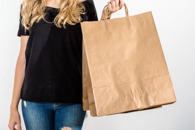 Junge glückliche frau mit den einkaufstaschen lokalisiert auf grauem hintergrund
