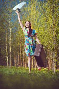 Junge glückliche frau mit einem koffer und einer karte, die jemandem eine hand winkt