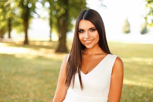 Junge glückliche frau mit einem lächeln in einem weißen kleid an einem sommertag nahe bäumen