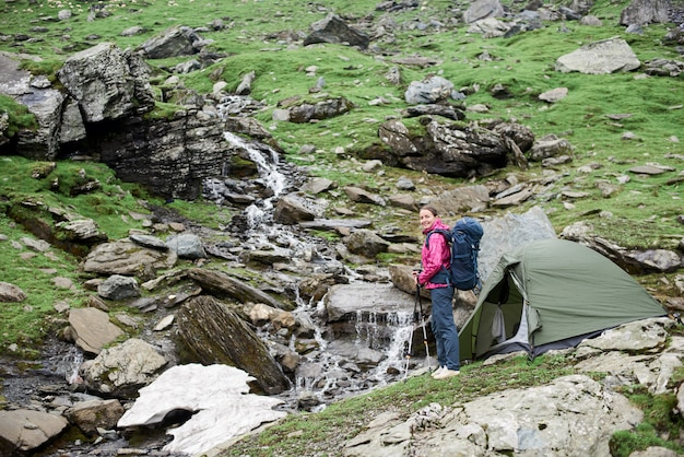 Junge glückliche frau mit einem rucksack nahe einem zelt mit einem schönen blick auf einen berg