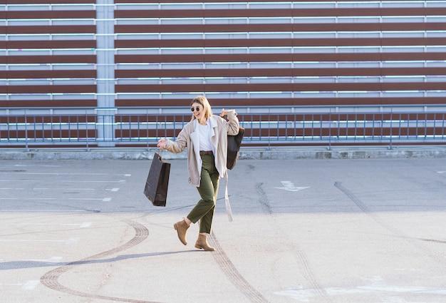 Junge glückliche frau mit einkaufstaschen, die auf straße gehen.