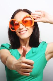 Junge glückliche frau mit großer orangefarbener sonnenbrille