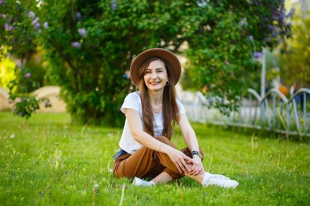 Junge glückliche frau mit hut sitzt auf einem grünen rasen in einem park. ein mädchen von europäischem aussehen mit einem lächeln im gesicht an einem strahlend sonnigen sommertag