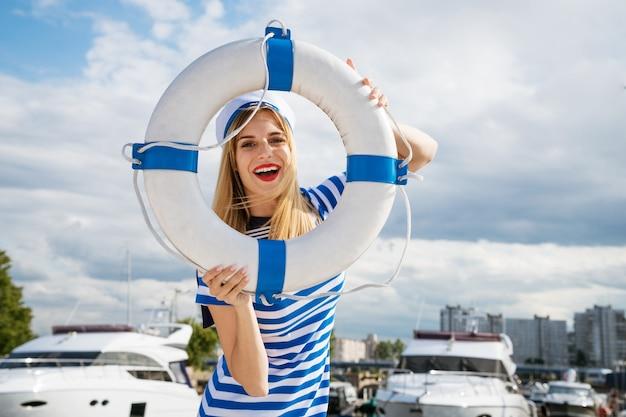 Junge glückliche frau mit kaukasischem aussehen in einem blau gestreiften kleid, die auf einer yacht steht und mit einem rettungsring in der hand gegen die oberfläche eines blauen himmels mit wolken an einem sonnigen sommertag posiert
