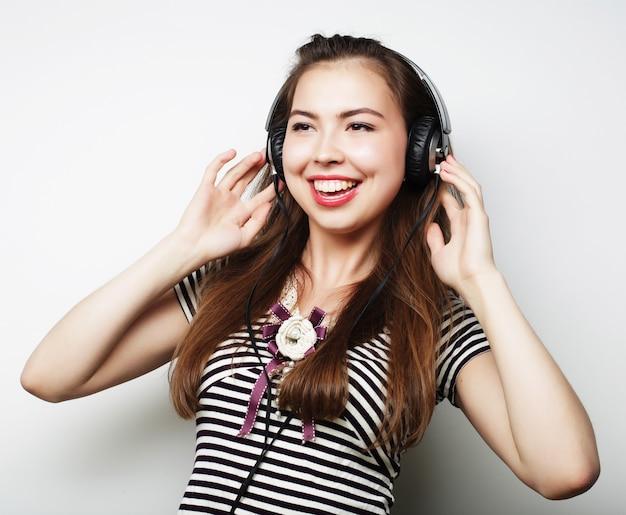 Junge glückliche frau mit kopfhörern, die musik auf grau hören
