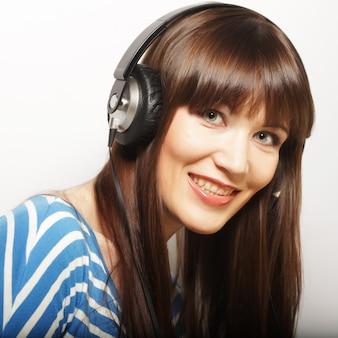 Junge glückliche frau mit kopfhörern, die musik hören