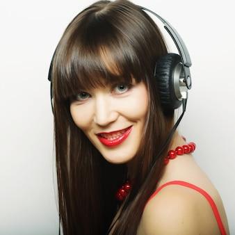 Junge glückliche frau mit kopfhörern, die tomusik hören