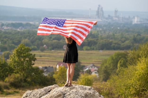 Junge glückliche frau mit langen haaren, die auf dem wind wehende amerikanische nationalflagge in ihren händen, die auf einem hohen felsigen hügel steht und einen warmen sommertag genießt.