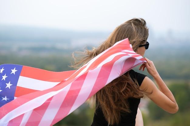 Junge glückliche frau mit langen haaren, die auf der amerikanischen nationalflagge des windes winken