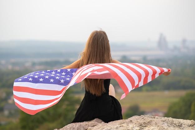 Junge glückliche frau mit langen haaren, die auf wind amerikanische nationalflagge auf ihren sholders winken, die draußen ruhen und warmen sommertag genießen.