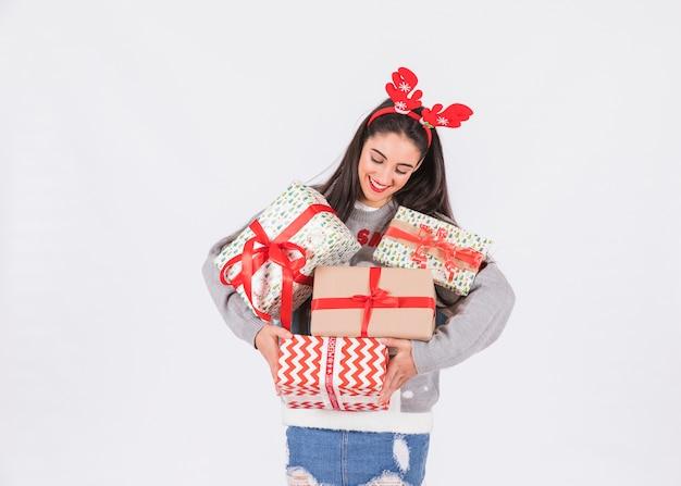 Junge glückliche frau mit rotwildgeweihstirnband und präsentkartons