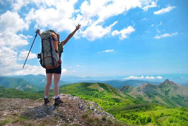 Junge glückliche frau mit wanderstock, rucksack, der auf dem felsen mit erhobenen händen steht und zu grüner landschaft schaut