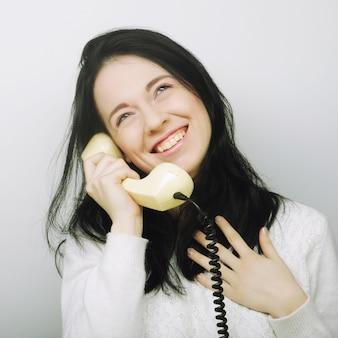 Junge glückliche frau mit weinlese-telefon