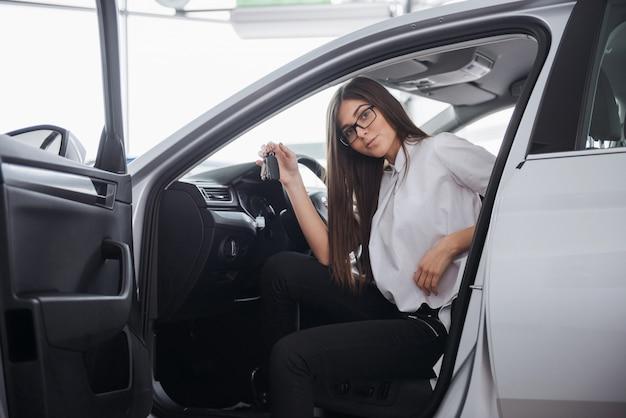 Junge glückliche frau nahe dem auto mit schlüsseln in der hand