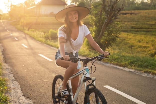 Junge glückliche frau reitet fahrrad durch schmale landstraße