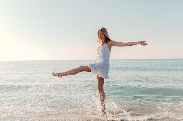 Junge glückliche frau tanzt herum und dreht sich am sonnigen sommermode-stil des seestrandes im weißen kleid urlaub