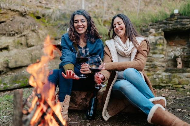 Junge glückliche frauen, die glas rotwein trinken. frauen, die sich neben dem feuer erwärmen. lagerfeuer, outdoor-aktivitäten konzept.