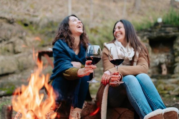 Junge glückliche frauen, die lachen und glas rotwein halten. frauen, die sich neben dem feuer erwärmen. lagerfeuer, outdoor-aktivitäten konzept.