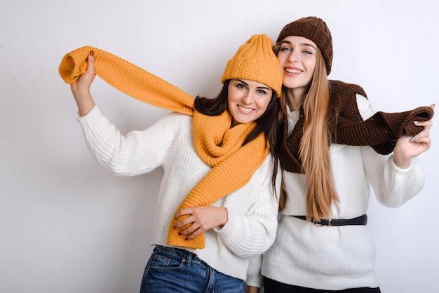 Junge glückliche frauen, die tragenden schal und kappe des winters auf einem grauen hintergrund genießen