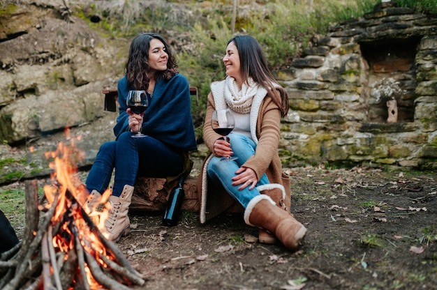 Junge glückliche frauen, die zusammen sprechen, während sie glas rotwein trinken. frauen, die sich neben dem feuer erwärmen. lagerfeuer, outdoor-aktivitäten konzept.