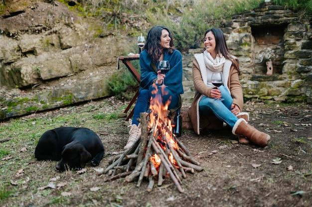 Junge glückliche frauen, die zusammen sprechen, während sie glas rotwein trinken. frauen, die sich neben dem feuer mit ruhendem hund erwärmen. lagerfeuer, outdoor-aktivitäten konzept.