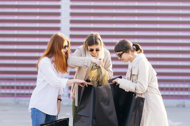 Junge glückliche frauen mit einkaufstaschen, die auf straße gehen.