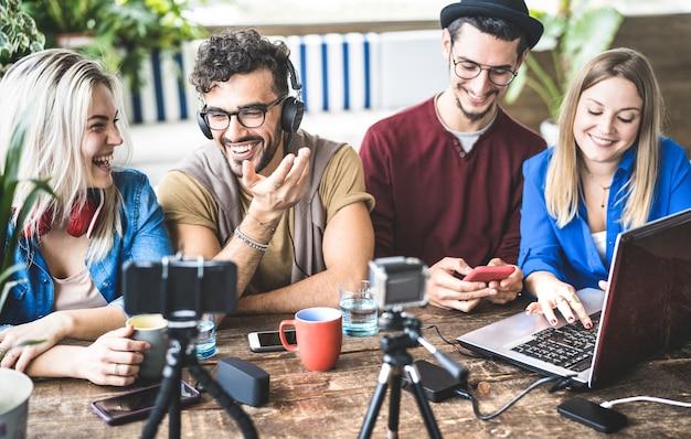 Junge glückliche freunde, die inhalt auf streaming-plattform mit digitaler webkamera teilen