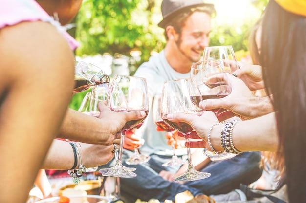 Junge glückliche freunde, die zusammen spaß in einem picknick am hinterhof zujubeln und haben