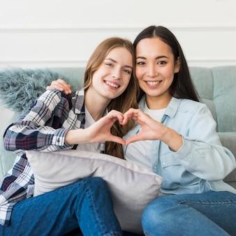 Junge glückliche freundinnen, die herzzeichen zeigen
