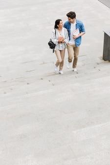 Junge glückliche fröhliche erstaunliche liebevolle paarstudenten im freien, die mit büchern schritt für schritt gehen.