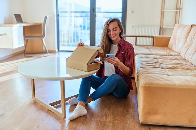 Junge glückliche, fröhliche lächelnde mädchen kunden erhielten paket und auspacken karton mit online-shop-bestellung, guter versand lieferservice delivery