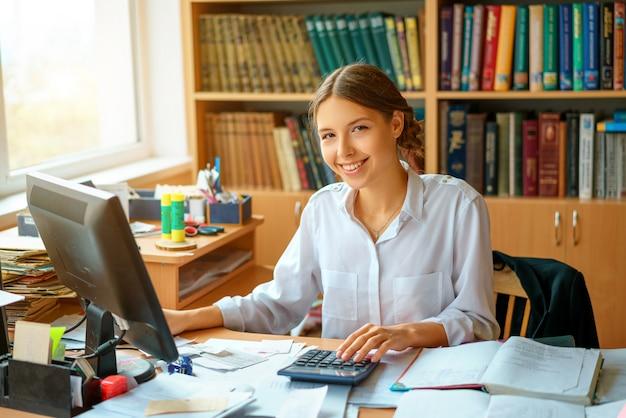 Junge glückliche geschäftsdame im weißen hemd, das bei tisch mit computer- und papierarbeitsumgebung sitzt.