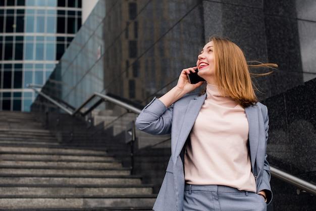 Junge glückliche geschäftsfrau, die am telefon in einem bürogebäude spricht.