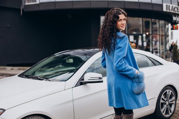 Junge glückliche geschäftsfrau, die aus ihrem auto geht
