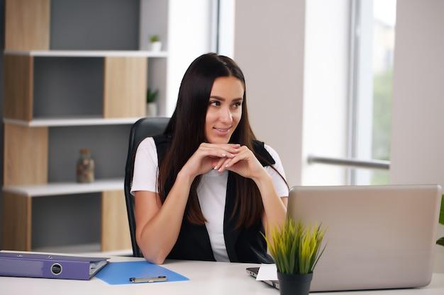 Junge glückliche geschäftsfrau im büro, die am laptop arbeitet