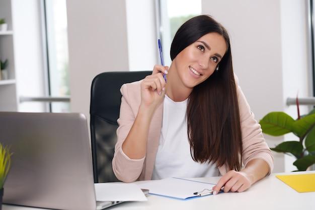 Junge glückliche geschäftsfrau im büro, notizen in einem notizbuch machend