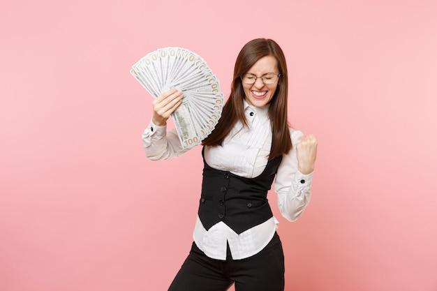Junge glückliche geschäftsfrau in den gläsern, die bündel viele dollar halten, bargeld, das siegergeste einzeln auf rosafarbenem hintergrund tut. chefin. erfolg karriere reichtum. kopieren sie platz für werbung.